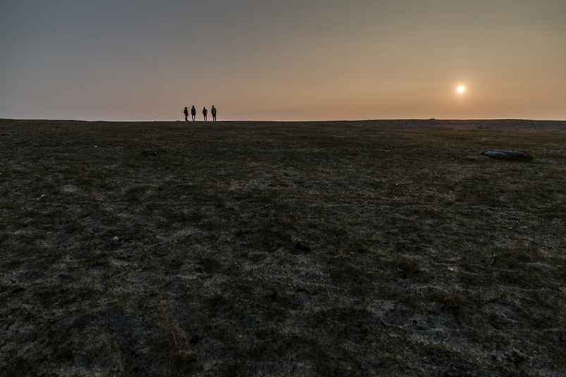 Figures standing on the horizon at sunset
