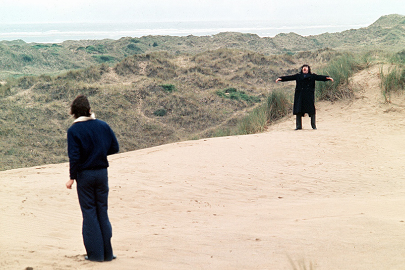 Two people dressed in black in sand dunes